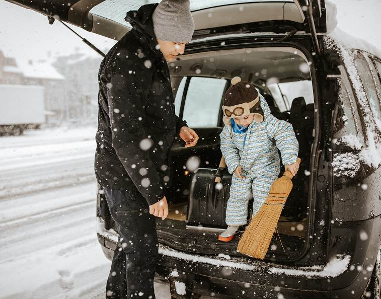 Father and son getting out of a car in the snowy winter.