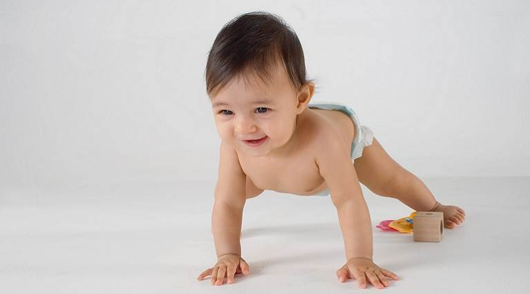 Baby crawling with a diaper on.